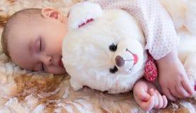 Baby sleeping with teddy bear Stock Image