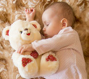 Baby sleeping with teddy bear Stock Photos