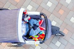 Baby sleeping three-wheel stroller outdoor. Child in bright casual costume lying at big comfortable pram. Parent walking with carr royalty free stock image