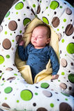 Baby sleeping. In a warm comfy blanket surrounded by a nursing pillow Stock Photo