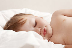 Baby sleeping in white bed Stock Image