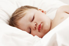 Baby sleeping in white bed royalty free stock photography