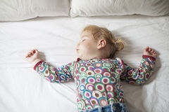 Baby sleeping on white bed. Blonde caucasian baby face nineteen month age with colored shirt sleeping on white sheets king bed royalty free stock images