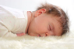 Baby sleeping on white fur. Royalty Free Stock Photos
