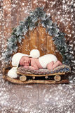 The baby is sleeping in wooden sledges. New year`s Eve Royalty Free Stock Photo