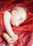 The  baby sleeping and wrapped up in red calico material Royalty Free Stock Photos