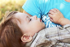 Baby sleeps in the arms of her mother. stock photography