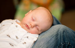 A baby sleeps comfortably on his father's lap Royalty Free Stock Photo