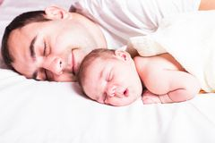 Baby sleeps with dad Stock Images
