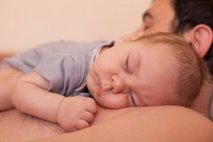 Baby sleeps on dad Stock Image