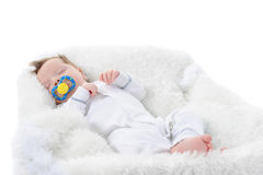 Baby sleeps with a pacifier in her mouth Stock Images