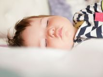 Baby sleeps in parents bed. arms outstretched baby`s restful sleep. close-up. child 0-1 years old. adorable lovely baby sleeps