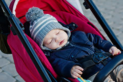 Baby sleeps in a red stroller Royalty Free Stock Photography