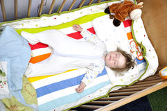 Baby sleeps star style in bed Stock Image