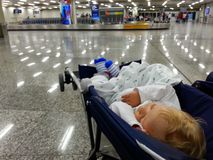 Baby sleeps in stroller while waiting for bags on an airport Stock Images