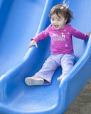 Baby Slide. A happy baby girl slides at the playground Royalty Free Stock Photo
