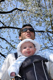 Baby in a sling. Father carrying a little child in a sling under the flowering cherry tree Stock Photo