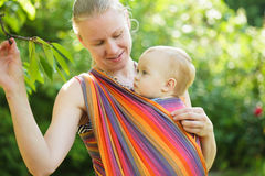 Baby in sling stock images