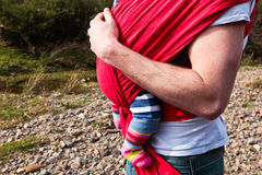 Baby sling. Young father carrying a baby girl in a carrier sling Royalty Free Stock Photos