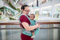Baby in slinger binnen Weinig babyjongen en haar moeder die in warenhuis lopen stock fotografie