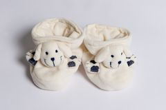 Baby slippers. White slippers for newborn with smiling doggies Stock Image