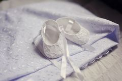 Baby slippers. On a beautiful white embroidered bedspread baby slippers are Royalty Free Stock Image