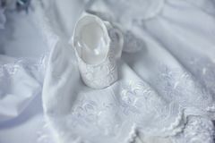 Baby slippers. On a beautiful white embroidered bedspread baby slippers are Royalty Free Stock Images