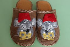Baby slippers with mouses. Slippers are brown with mouses in red caps and a piece of cheese royalty free stock images