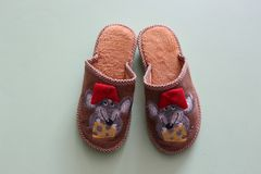 Baby slippers with mouses. Slippers are brown with mouses in red caps and a piece of cheese stock images