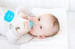 Baby with small bottle in bed Royalty Free Stock Images
