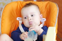 Baby with a small bottle sits on chair Royalty Free Stock Photography