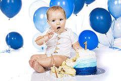 Baby smashing cake. A one year old baby boy smashing a blue iced birthday cake on a silver board with lots of blue helium balloons in the background Stock Images