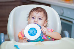 Baby smile eating in the kitchen on the sittting on the table Stock Photo