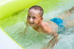 Baby with a smile floats in the pool. Boy bathes in baby pool Royalty Free Stock Photos