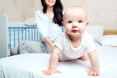Baby with smile hanging out on a bed in a room with  mother. The. Child smiles, Mom laughs Stock Images