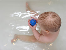 Baby with smile toy in bath Stock Image