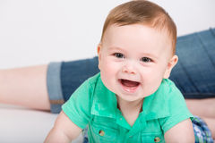 Baby Smiles on Stomach in Clothes. 8 month year old baby lays on his stomach looking towards camera, while mom is sitting in background. dressed in a cute green Stock Image