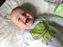 Baby Smiling. Baby Boy smiling with frog smiling too Royalty Free Stock Photography