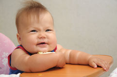 Baby smiling in the bucket seat Stock Images