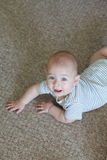 Baby smiling on carpet Stock Photography