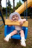 A little girl in a hat riding in a swing. The baby is smiling from a fun trip on a swing. She plays in a blue swing, on the street, in the Playground, wearing a royalty free stock photos