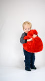 Baby smiling and hugging a plush heart Stock Photo