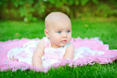 Baby smiling and looking up to camera outdoors in sunlight Stock Photo