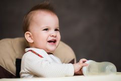Baby smiling mother and playing with a bottle Stock Image