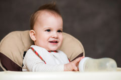 Baby smiling mother and playing with a bottle Stock Photography