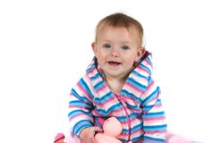 Baby Smiling with Toy. A cute baby in stripes holding a toy and smiling on white background Stock Image