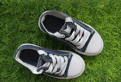 Baby sneakers on the green grass. top view stock photos