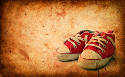 Baby sneakers on grunge paper Royalty Free Stock Photo