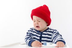 The baby sneezes with thermometer. The baby sneezes sitting in a chair in a red hat and a vest with a thermometer in his hand, his eyes are closed Stock Image