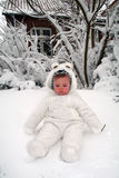 Baby snow. Baby in the snow in white snow suite. winter image of child with house in background Stock Photo